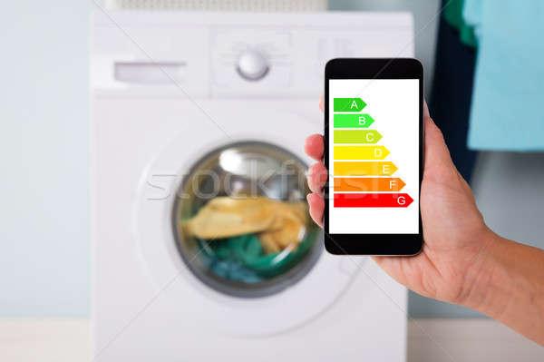 Hand Using Energy Label On Mobile Phone Against Washing Machine Stock photo © AndreyPopov
