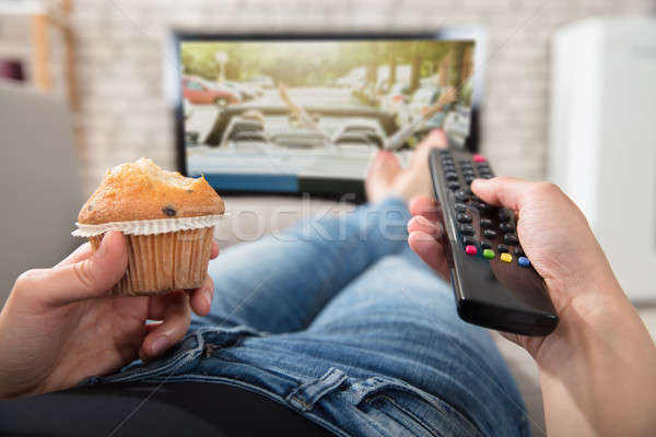 Woman Holding Cupcake And Remote Control In Hand Stock photo © AndreyPopov