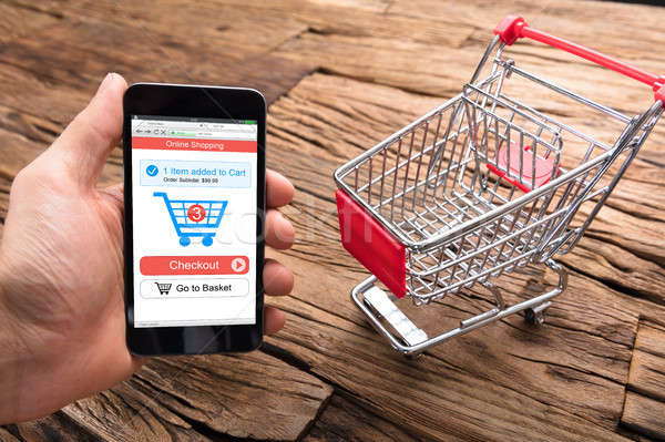Businessman's Hand Holding Smartphone By Shopping Cart On Table Stock photo © AndreyPopov