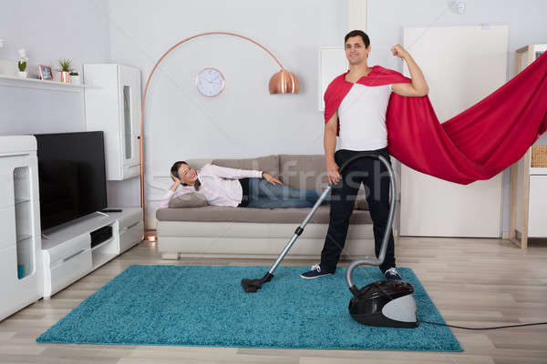 Woman Looking At Her Husband Cleaning Carpet With Vacuum Cleaner Stock photo © AndreyPopov
