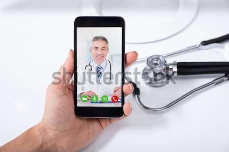 Doctor Video Conferencing With Male Colleague On Digital Tablet Stock photo © AndreyPopov