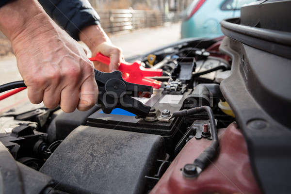 Stock photo: Person Using Jumper Cables To Charge Car's Dead Battery