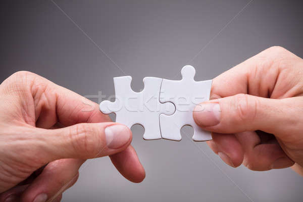 Close-up Of Businesspeople Holding Jigsaw Puzzle Stock photo © AndreyPopov