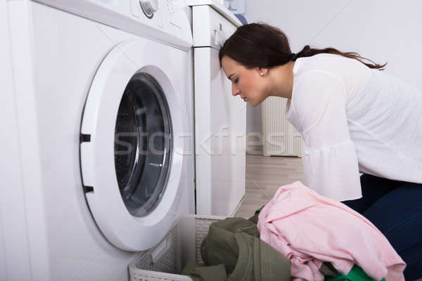 Side View Of An Exhausted Young Woman In Laundry Room Stock photo © AndreyPopov