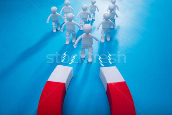 Elevated View Of Horseshoe Magnet Attracting Human Figures Stock photo © AndreyPopov