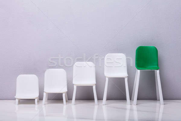 Increasing Scale Of White And Green Chairs In A Row Stock photo © AndreyPopov