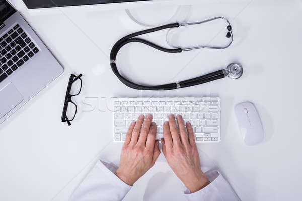 Elevated View Of A Doctor's Hand Typing On Computer Keyboard Stock photo © AndreyPopov