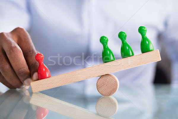 Person's Hand Balancing Pawns On Wooden Seesaw Stock photo © AndreyPopov