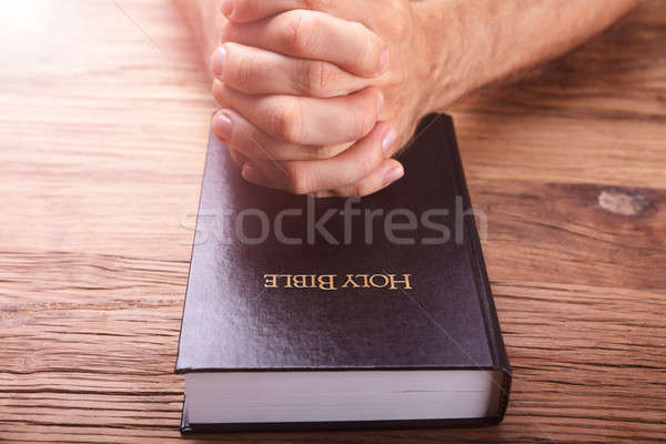 Man's Praying Hands On Bible Stock photo © AndreyPopov