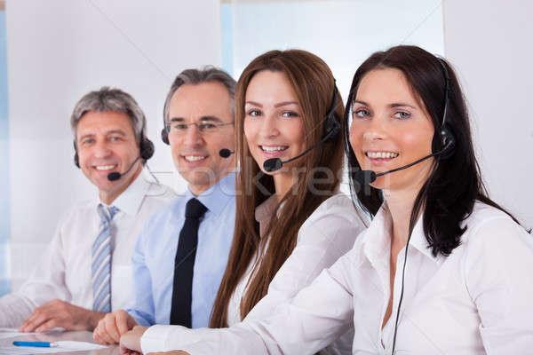 Gens d'affaires parler micro heureux séance rangée Photo stock © AndreyPopov