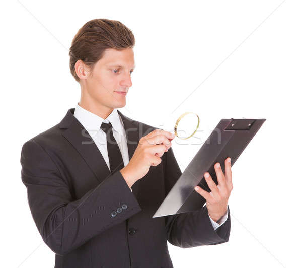 Man Looking Through Magnifying Glass On Clipboard Stock photo © AndreyPopov