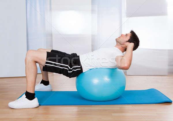 Man Doing Sit Ups On Fitness Ball Stock photo © AndreyPopov
