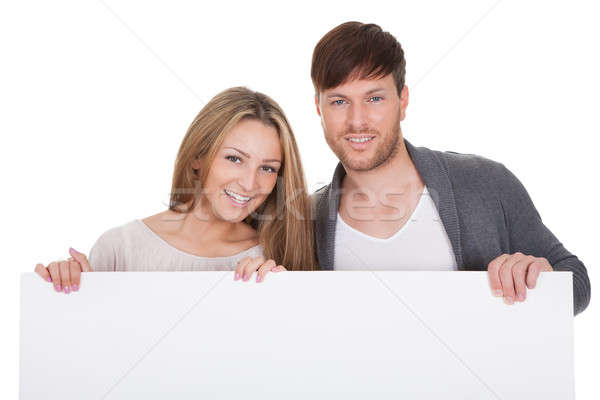 Positive young couple with blank board Stock photo © AndreyPopov