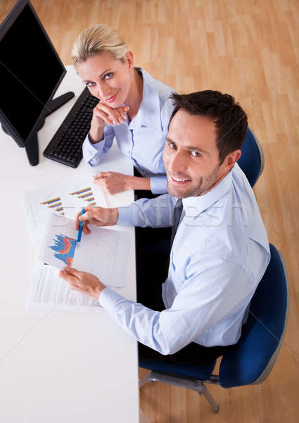 Smiling business colleagues discussing statistics Stock photo © AndreyPopov