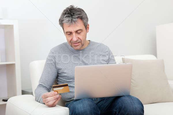 Senior man shopping at home using laptop Stock photo © AndreyPopov