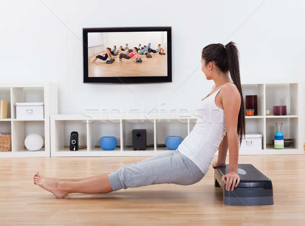 Athletic woman doing exercises in her livingroom Stock photo © AndreyPopov