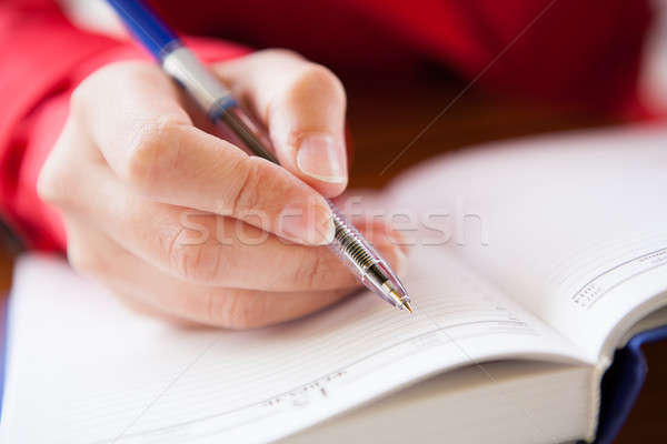 Close-up of hand writing in diary Stock photo © AndreyPopov