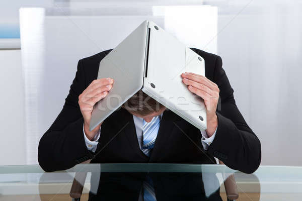 Depressed businessman hiding under his laptop Stock photo © AndreyPopov