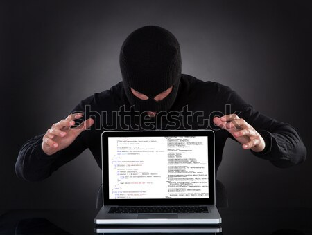 Man or hacker stealing data from a laptop at night Stock photo © AndreyPopov
