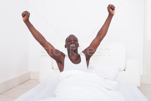 Man Raising Arm In Bedroom Stock photo © AndreyPopov