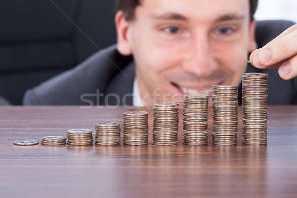 Happy Businessman Stacking Coins At Desk Stock photo © AndreyPopov