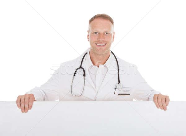 Happy Male Doctor Displaying Billboard Stock photo © AndreyPopov