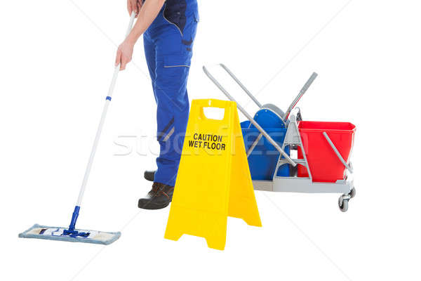 Low Section Of Servant Mopping Floor By Wet Floor Sign Stock photo © AndreyPopov