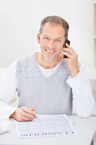Adam gazete konuşma cep telefonu okuma İlanlar Stok fotoğraf © AndreyPopov