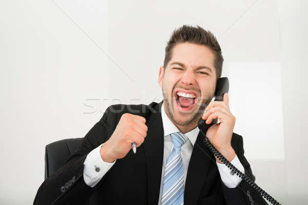 Businessman Screaming While Using Landline Phone In Office Stock photo © AndreyPopov