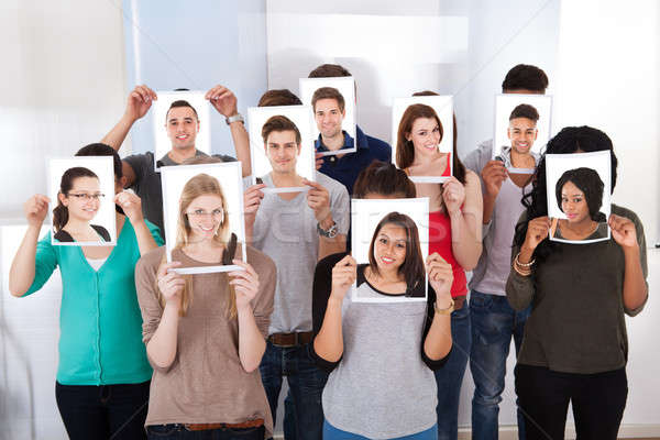 College Students Holding Photographs In Front Of Faces Stock photo © AndreyPopov