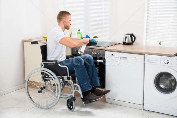 Handicapés homme nettoyage poêle jeunes fauteuil roulant Photo stock © AndreyPopov