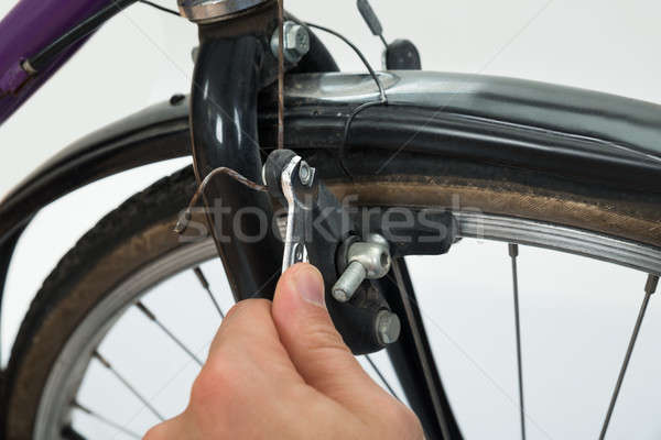 Person Hands Tightening Bolt Of Bicycle Tire Stock photo © AndreyPopov