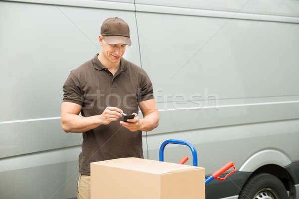 Mensajero lista teléfono móvil jóvenes feliz caja de cartón Foto stock © AndreyPopov