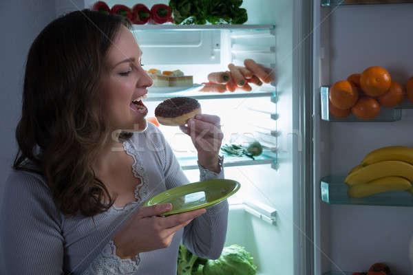 ストックフォト: 女性 · 食べ · ドーナツ · 冷蔵庫 · 若い女性 · オープン