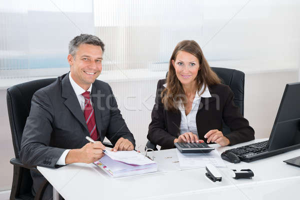 Two Businesspeople Calculating Tax In Office Stock photo © AndreyPopov