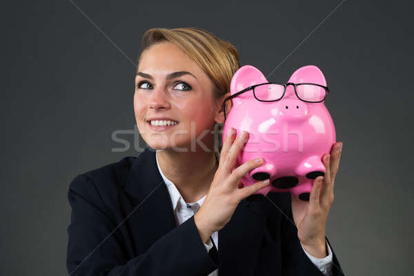 Businesswoman Shaking Piggybank Over Gray Background Stock photo © AndreyPopov