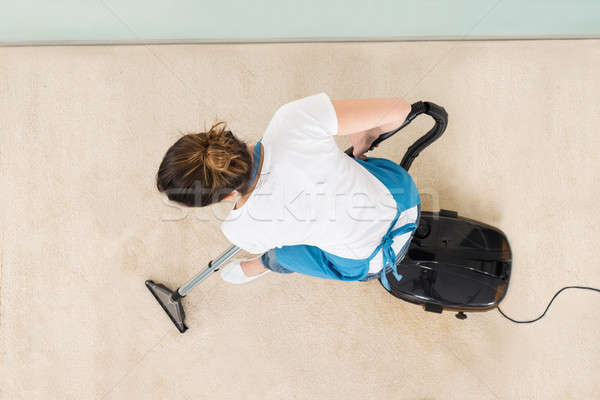 Young Female Janitor Vacuuming Floor Stock photo © AndreyPopov