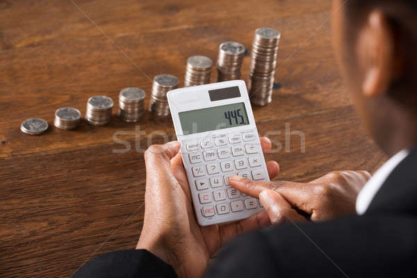 Zdjęcia stock: Kobieta · interesu · Kalkulator · monet · biurko
