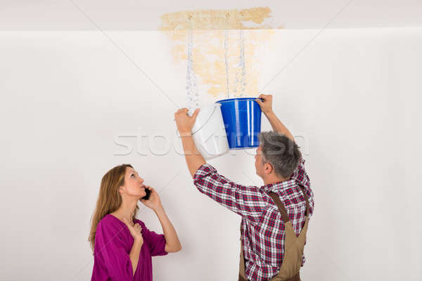 Stock photo: Worker Collecting Water In Bucket From Ceiling