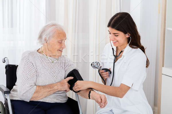 Female Doctor Checking Blood Pressure Of Senior Woman Stock photo © AndreyPopov