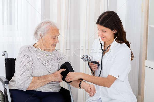 Női orvos vérnyomás idős nő boldog Stock fotó © AndreyPopov