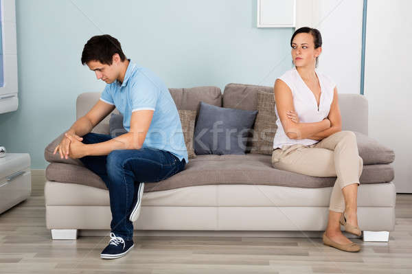Couple Sitting Back To Back On Sofa Stock photo © AndreyPopov