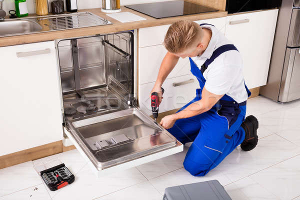 Tamir bulaşık makinesi genç hizmet işçi Stok fotoğraf © AndreyPopov