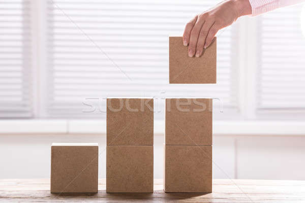 Human Hand Holding A Block To Complete Growth Bar Graph Stock photo © AndreyPopov