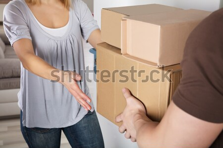 Delivery Man Giving Parcel Box To Young Woman Stock photo © AndreyPopov