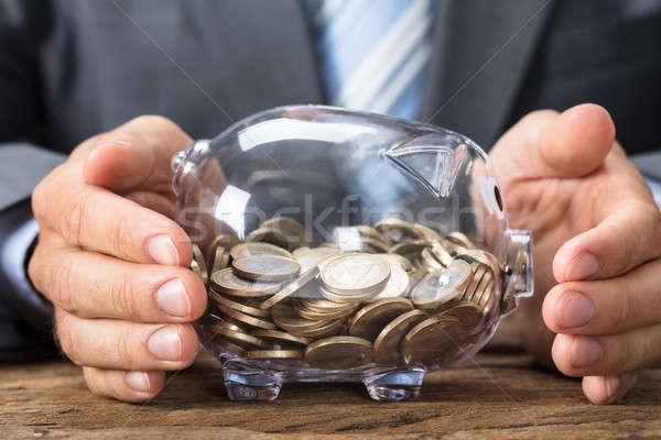 Empresário transparente piggy bank moedas tabela Foto stock © AndreyPopov