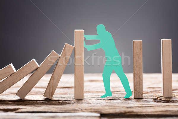 Green Paper Man Stopping Wooden Domino Blocks Stock photo © AndreyPopov