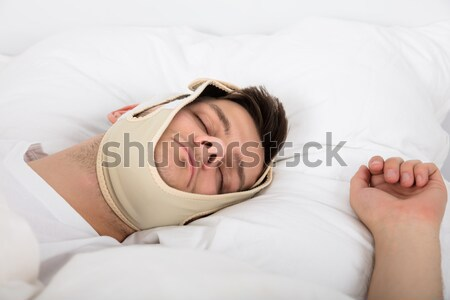 Man Sleeping With Anti Snoring Bandage Stock photo © AndreyPopov