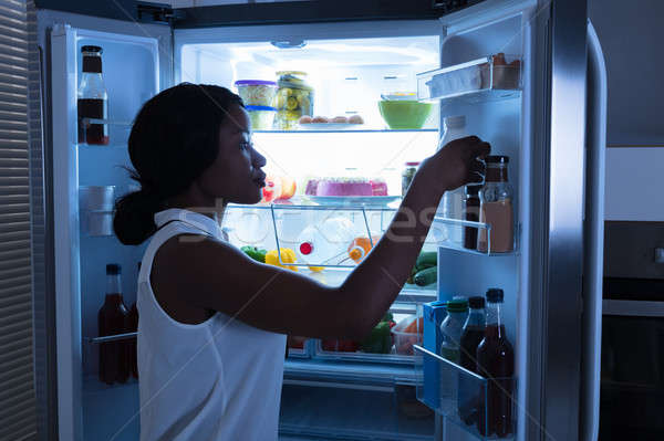 Woman Taking Out Bottle From Refrigerator Stock photo © AndreyPopov