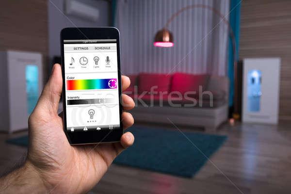 Menselijke hand elektrische licht mobiele telefoon home Stockfoto © AndreyPopov